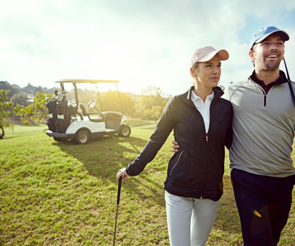 Shot of a smiling young couple enjoying a day on the golf course